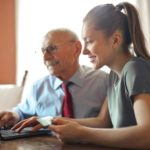 young-woman-helping-senior-man-with-payment-on-internet-using-laptop